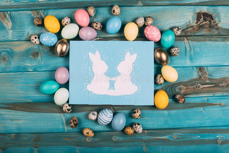 Top view of colorful easter greeting card with rabbits and colorful eggs around on blue. Wooden planks royalty free stock photo