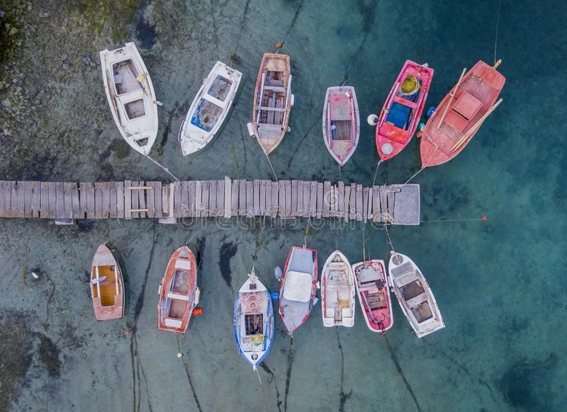 A top view of colorful fishing boats anchoring in marina next to jetty wooden pier. Greece royalty free stock photo