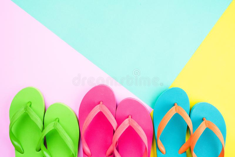 Top view of colorful flip flop on pink and yellow background for summer holiday and vacation concept stock images