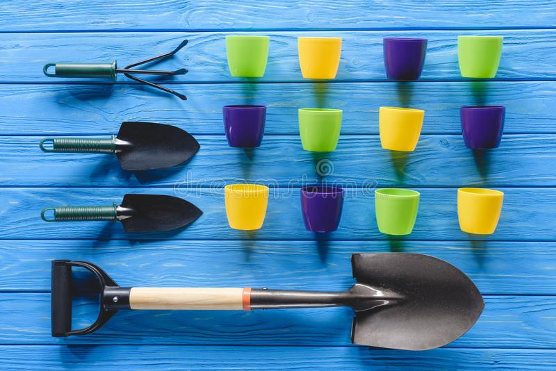 top view of colorful flower pots in row and gardening equipment on blue royalty free stock images