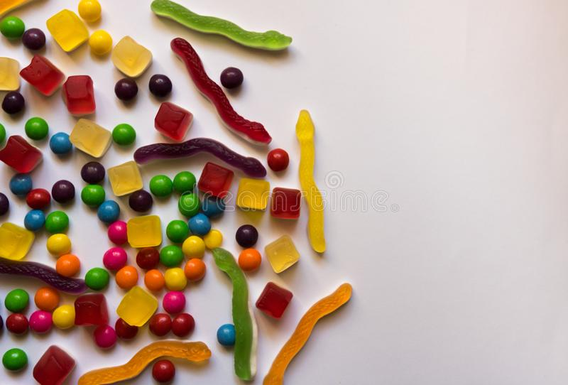 Top view of colorful hard and jelly candies on white background with copy space stock image