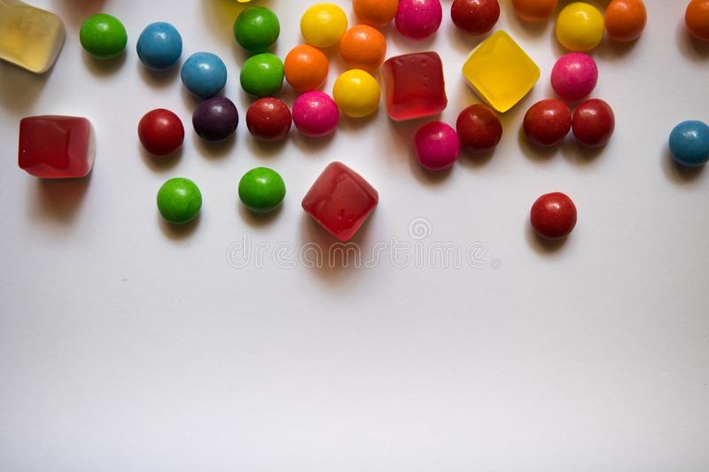 Top view of colorful hard and jelly candies on white background with copy space stock photography