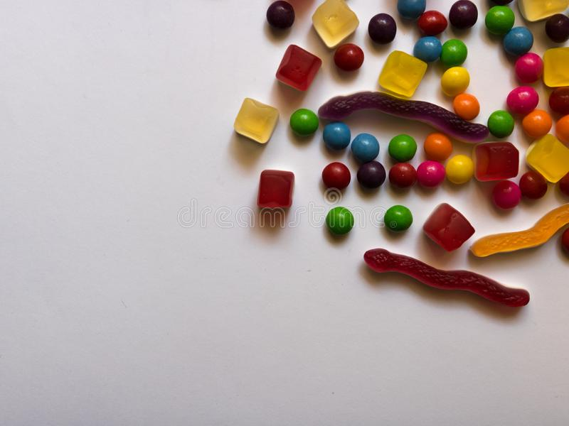 Top view of colorful hard and jelly candies on white background with copy space royalty free stock photography