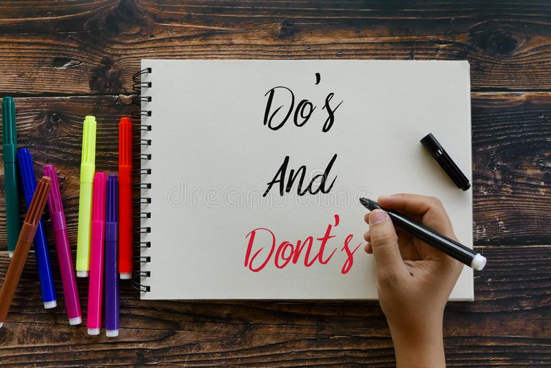 Top view of colorful pen and hand holding black pen writing Do& x27;s and Dont& x27;s on notebook on wooden background. Dos guidelines tips communication stock images