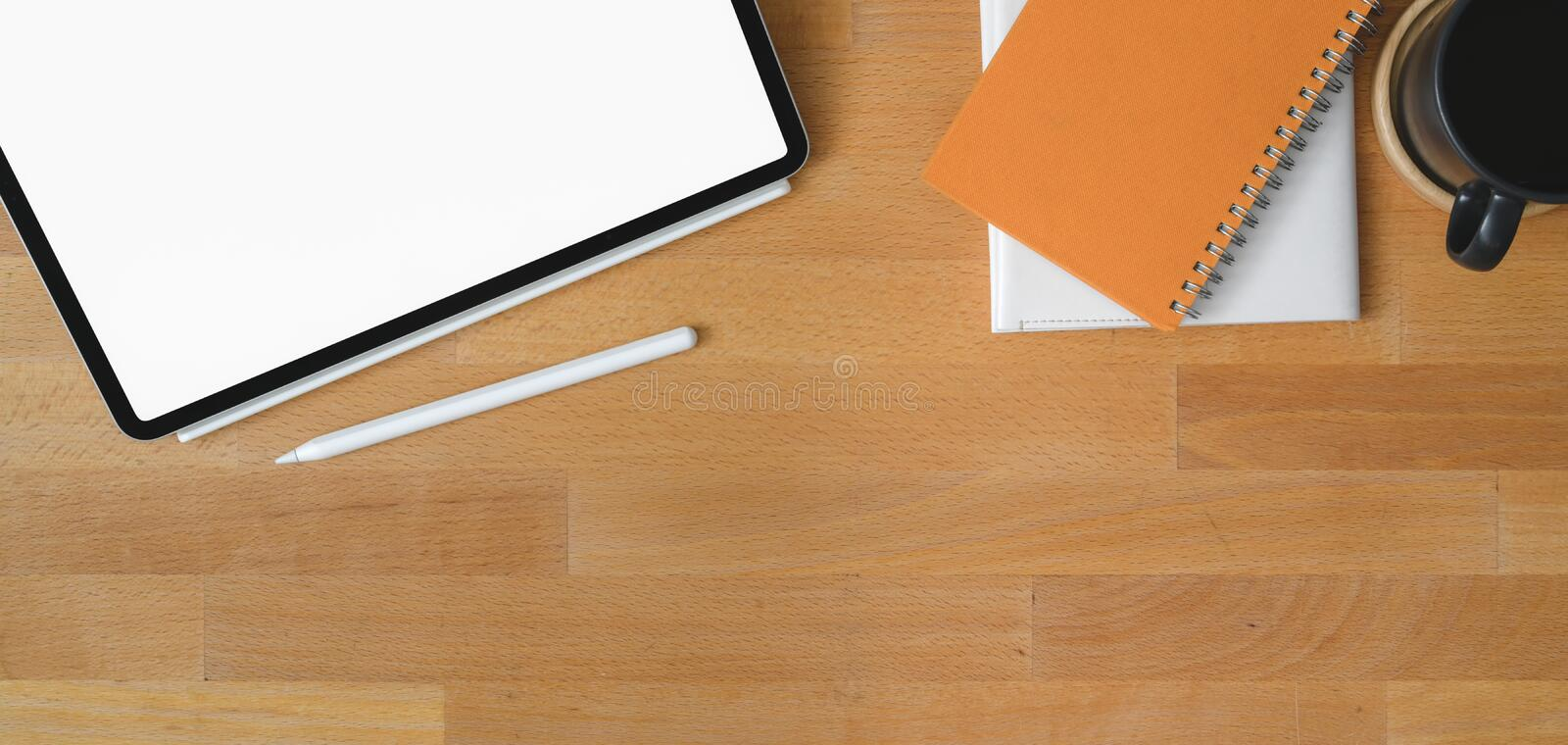 Top view of comfortable workplace with blank screen digital tablet and office supplies. On wooden table royalty free stock image