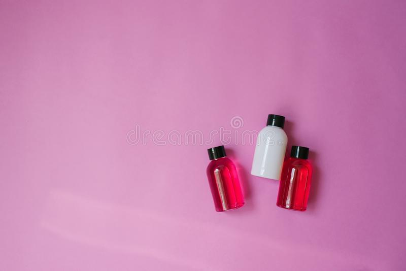Top view composition of small travel bottles for cosmetics, shower gel, shampoo and hair balm on a pink background. Concept of bod royalty free stock photography