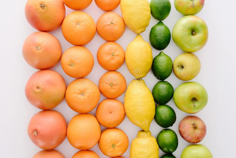 Top view of composition of various ripe fruits in rows. On white tabletop stock photo