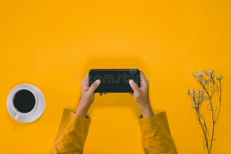 Top view concept of pastel yellow background, young woman handing pressing mobile phone. With a cup of coffee and a bouquet of stock photos