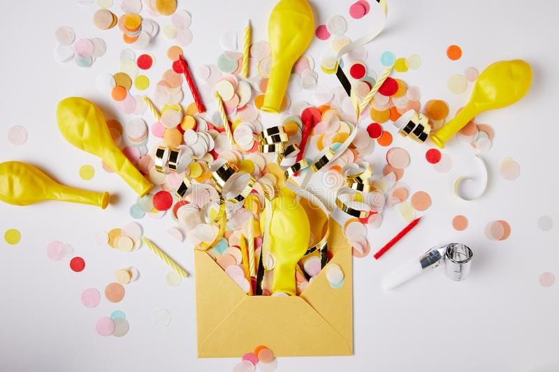 Top view of confetti pieces, balloons and yellow envelope on white surface royalty free stock photography