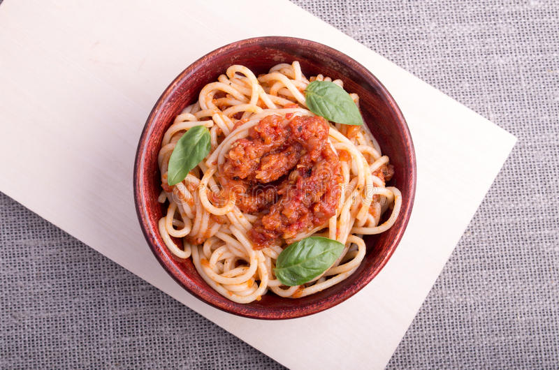 Top view of cooked spaghetti with tomato relish. And basil leaves in a brown small wooden bowl closeup on a wooden stand stock image