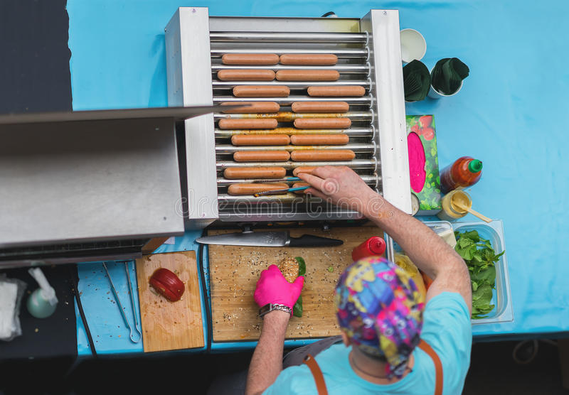 Top view of Cooking barbecue. Man with healthy vegan street food, sausages, Hot Dogs made with soy protein wiener stock image