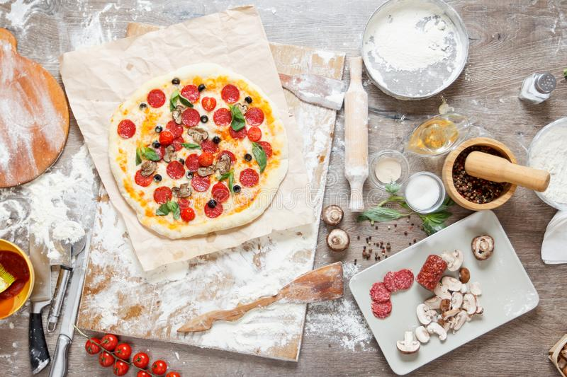 Top view cooking pizza with ingredients, tomatoes, salami and mushrooms on wooden tabletop. Top overhead view cooking pizza with ingredients, tomatoes, salami stock photo