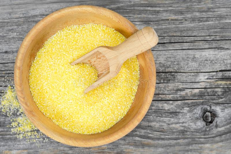 Cornmeal in wooden bowl. Top view of cornmeal in wooden bowl stock photo