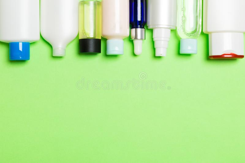 Top view of cosmetics bottles on green background. Skin care concept with space for your design.  stock image