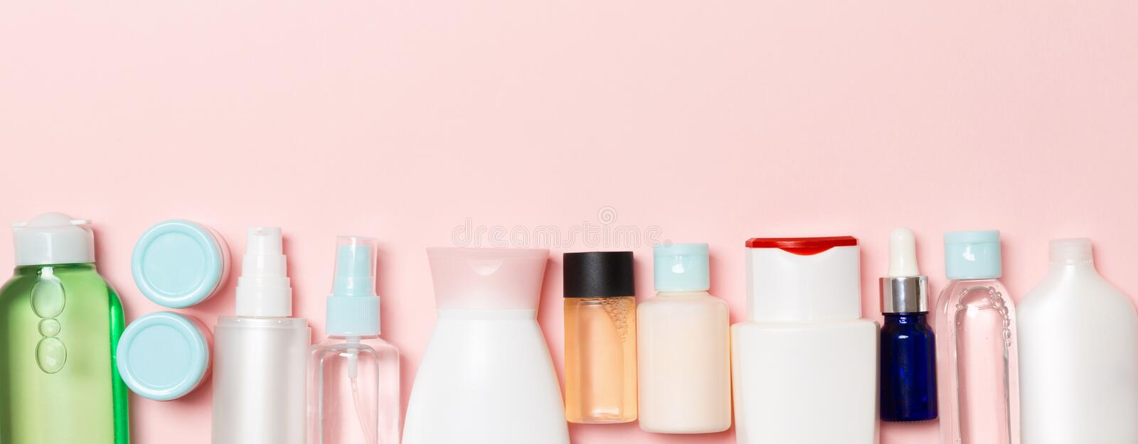 Top view of cosmetics bottles on pink background. Skin care concept with space for your design.  stock photography