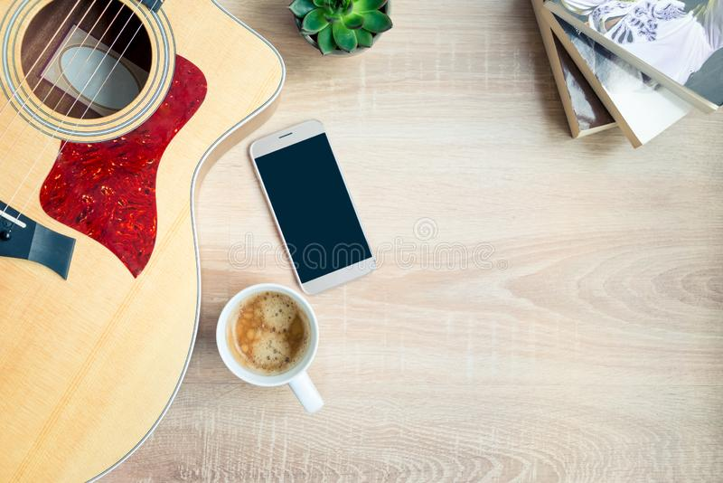 Top view of cosy home scene. Guitar, books, cup of coffee, phone and succulent plants over wooden background. Copy space, mock-up stock photos