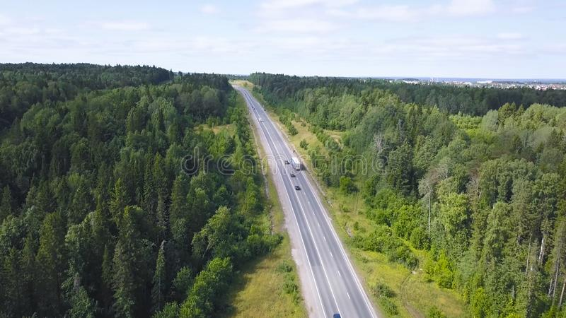 Top view of countryside highway in forest area. Clip. Rural road with traffic of cars and trucks going to city on royalty free stock images