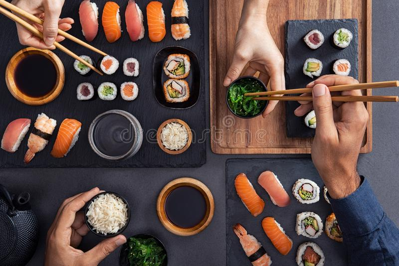 Sharing and eating sushi food. Top view of couple hands eating sushi food at japanese restaurant. High angle view of women hand serving seaweed in little bowl royalty free stock photography