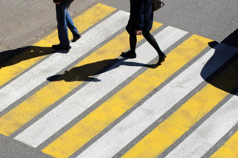 Top view of couple man and women people walk across crosswalk in the city street. Sunday stock image