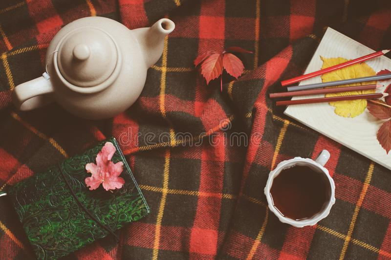 Top view of cozy autumn morning at home. Breakfast with pot of tea and bagel. With apples on woolen plaid blanket. Notebook with color pencils stock photography