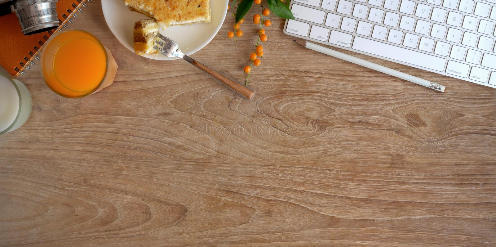Top view of cozy workspace with a glass of orange juice and toast bread on wooden table royalty free stock image