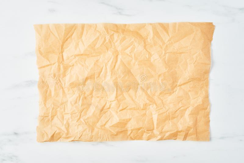 Top view of crumpled piece of parchment or baking paper on white marble table royalty free stock photo
