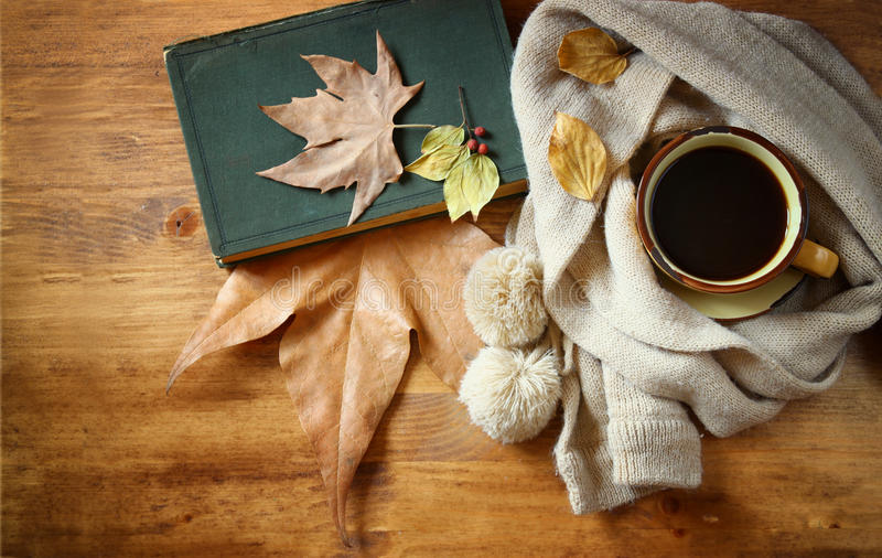 Top view of Cup of black coffee with autumn leaves, a warm scarf and old book on wooden background. filreted image royalty free stock images