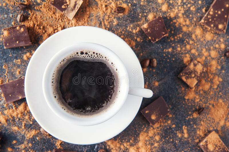 Top view cup of black coffee on a dark stone background with beans, cocoa powder and chocolate pieces scattered around. Selective. Focus. Space for text royalty free stock photo