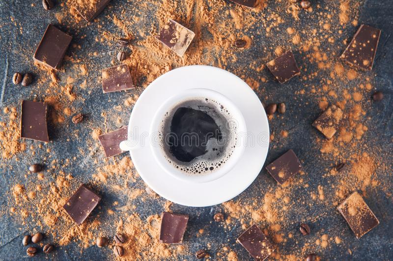 Top view cup of black coffee on a dark stone background with beans, cocoa powder and chocolate pieces scattered around. Selective. Focus. Space for text royalty free stock photography