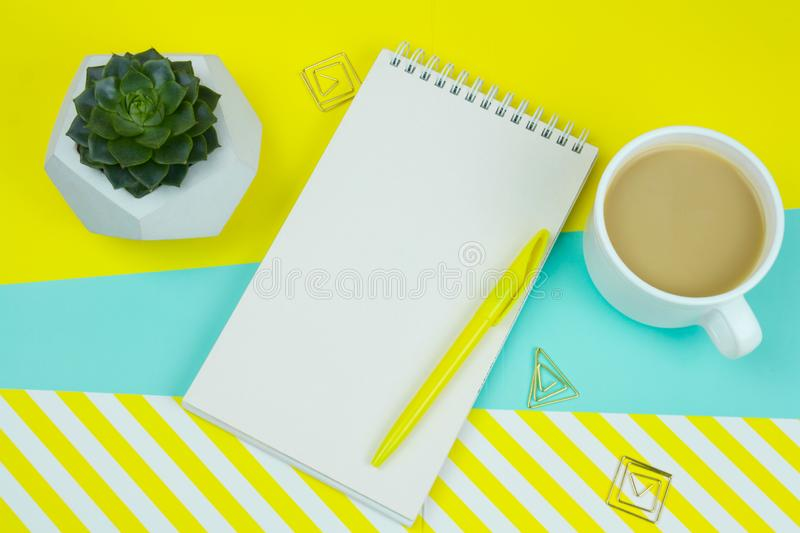 cup of coffe, notebook with blank paper sheet, pen, ppaer clips and sucuulent on a blue and stripped yellow background . royalty free stock photos