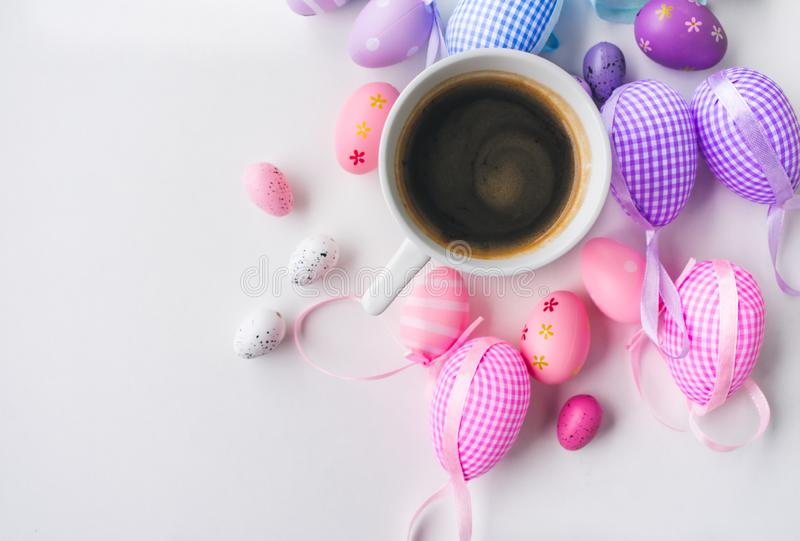 Top view of a cup of coffee and colorful Easter egg decorations on white background royalty free stock photo