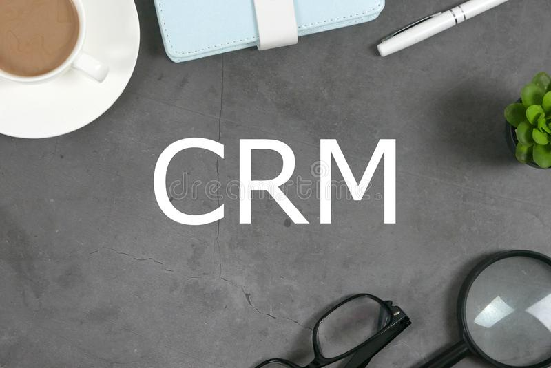 Top view of a cup of coffee,notebook,pen,plant,magnifying glass, and sunglasses on grey floor written with CRM. Customer royalty free stock photos
