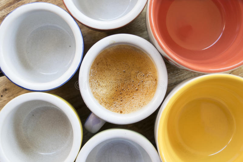 Top view of a cup of creamy espresso coffeee. Next to others empty cups royalty free stock photography