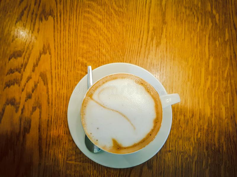 A cup of coffee, cafe latte, with milk foam, viewed from above on a brown wooden table surface stock photography