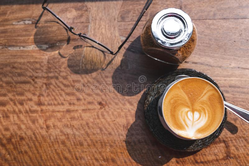 top view cup of hot milk coffee with latte art, smartphone, eye glasses and brown sugar on wooden desk in the morning light royalty free stock photos
