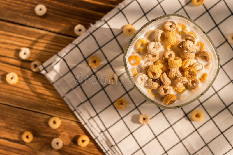Top view cup of milk with cereal rings in a sunny morning as healthy breakfast stock image