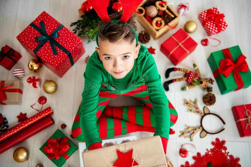 Top view of a curious young boy wearing xmas pajamas sitting on the floor, holding a christmas present. royalty free stock photography