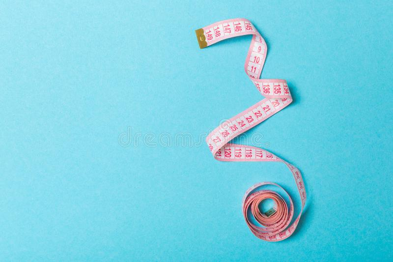 Top view of curled measuring tape as a sewing accessory on blue background. Tailor concept with copy space.  royalty free stock photo