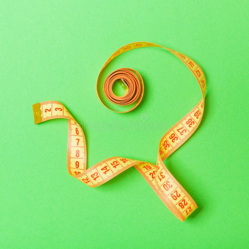 Top view of curled measuring tape as a sewing accessory on green background. Tailor concept with copy space.  royalty free stock photo