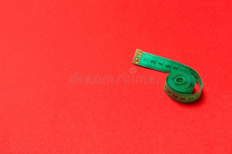 Top view of curled measuring tape as a sewing accessory on red background. Tailor concept with copy space.  stock images