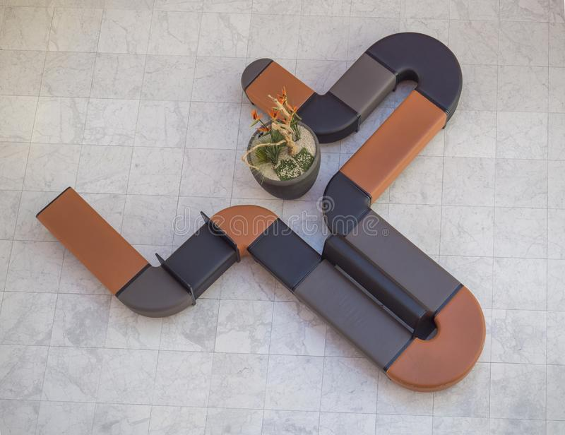 Top view of curved black and orange leather couch seating and flower pot in modern office hall with marble pavement stock images