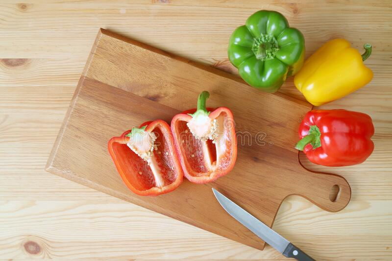 Top View of Cut Red Bell Pepper on a Cutting Board with Knife Surrounded by Tricolor Bell Peppers on Wooden Table. Healthy eating royalty free stock photos