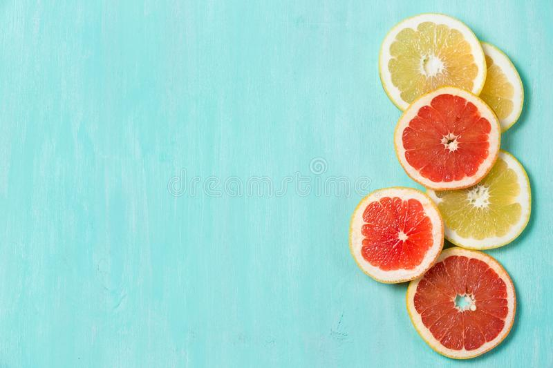Top view on cut red and yellow grapefruit on turquoise wooden background. Juicy and fresh fruit. Healthy eating concept.  royalty free stock photo