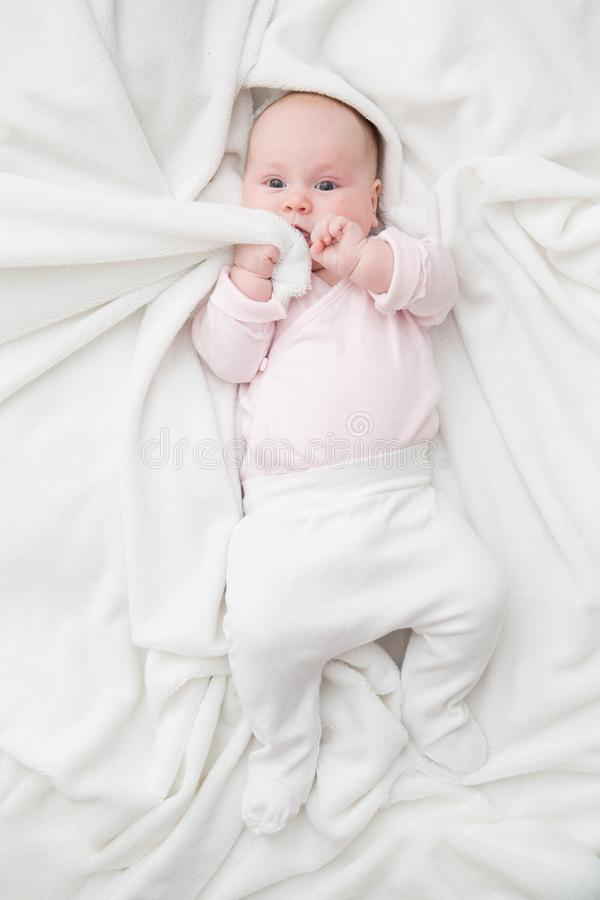 Top view of cute adorable baby girl wearing white body in bedroom looking at camera. Newborn child pulling blanket to stock image