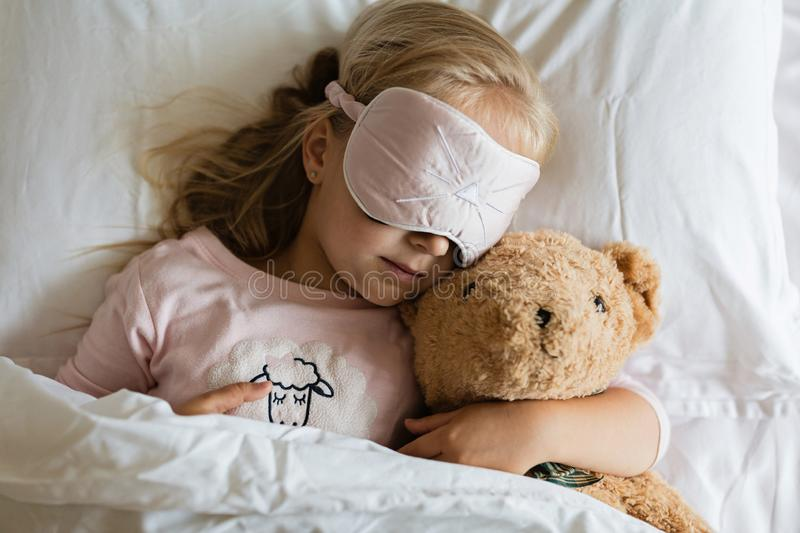 Top view of cute blonde little girl in pajamas and blindfold sleeping in white bed with teddy bear, awaking early in the morning stock photos