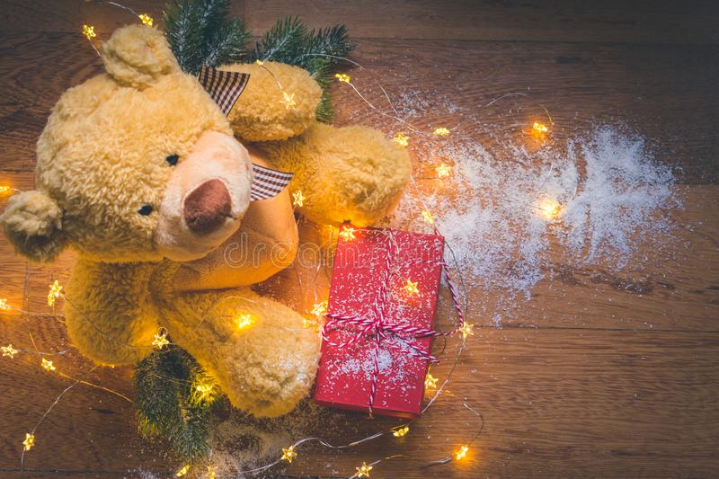View of a teddy with a red wrapped present, and Christmas decorations on wooden background royalty free stock photography
