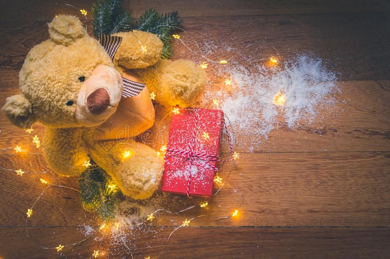 View of a teddy with a red wrapped present, and Christmas decorations on wooden background stock photography