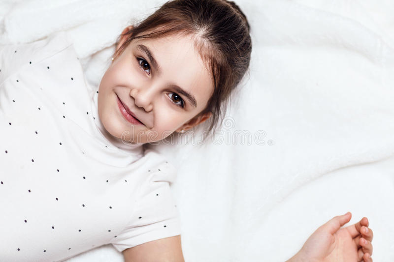 Top view on cute brunette girl lying on bed. royalty free stock photography