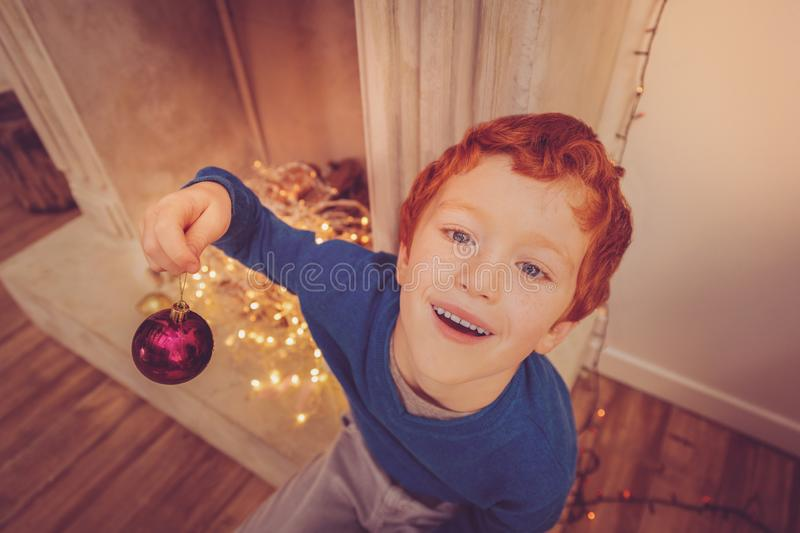 Top view of cute ginger-haired boy holding Christmas ball stock photography