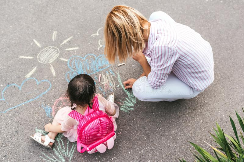 Top view of cute little girl and her mother drawing with colorful chalks on the sidewalk. Caucasian blonde female play together royalty free stock photos